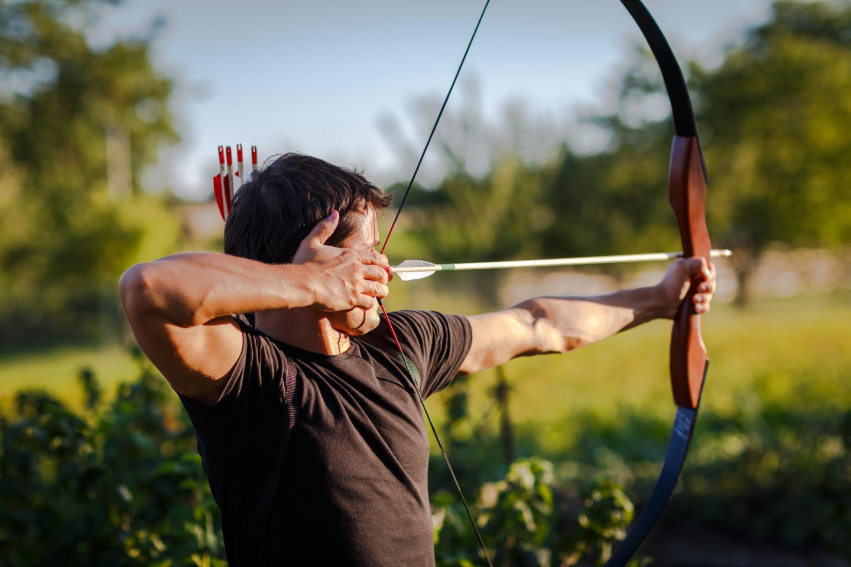 Ein Mann, der in der Natur mit dem Bogen zielt und abschießen möchte